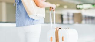 キャリーバッグを持って旅行に出かけるイメージ